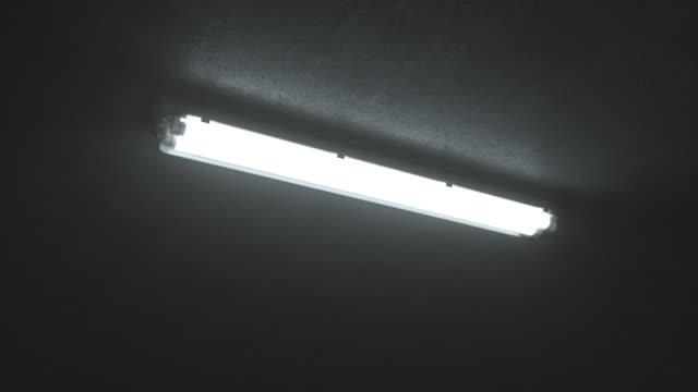 산업 건물에서 흰색 이중 형광 조명의 4k 샷이 켜집니다. 어둡고 차가운 방의 천장에. 닫아. 무서운 깜박이는 네온 불빛. - 불길한 스톡 비디오 및 b-롤 화면
