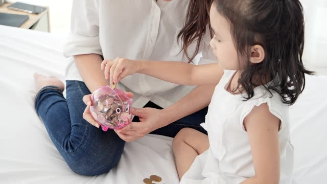 4k slow motion ,asian family depositing coins into piggy bank in white bed room. - soft focus video stock e b–roll
