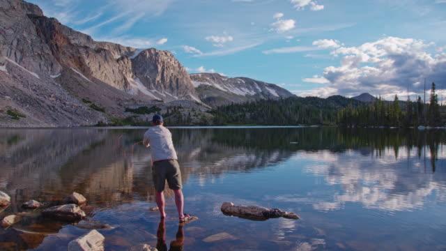 4k slow motion flugfiske i fjällsjö vid soluppgången - klippiga bergen bildbanksvideor och videomaterial från bakom kulisserna