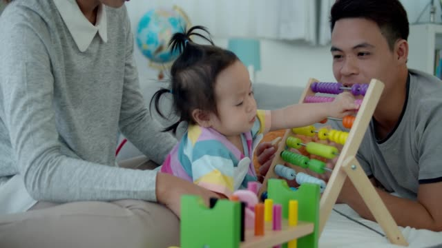 4k slowmotion,Asian family playing wooden multi color toy with baby girl.Education for baby concept.