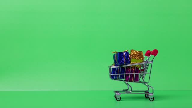 4k stop motion close-up of red shopping trolley taking gift box on green background.