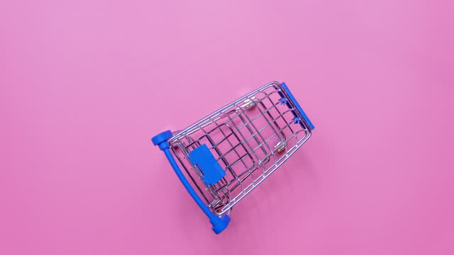 4k stop motion of Empty shopping cart on the blue background