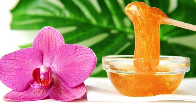 4k. sugar paste or wax honey for hair removing flows down from wooden waxing spatula sticks - depilation and beauty - szpatułka przybór do gotowania filmów i materiałów b-roll