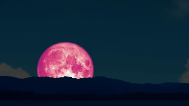 4k Super pink moon rise back on silhouette island on the night sky