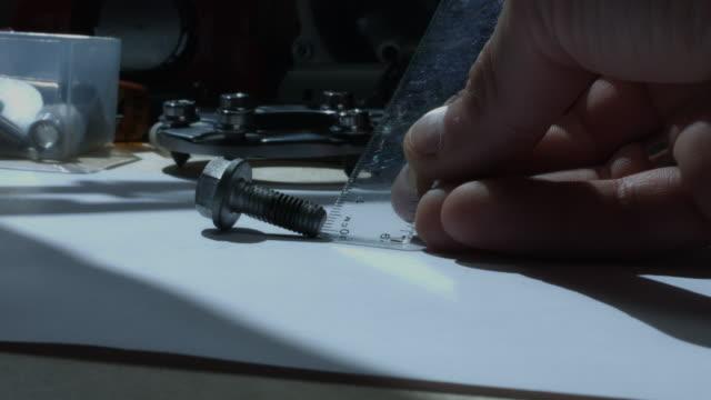 4 k technische zusammensetzung einer menschlichen hand messen eine schraube - steckschlüssel stock-videos und b-roll-filmmaterial