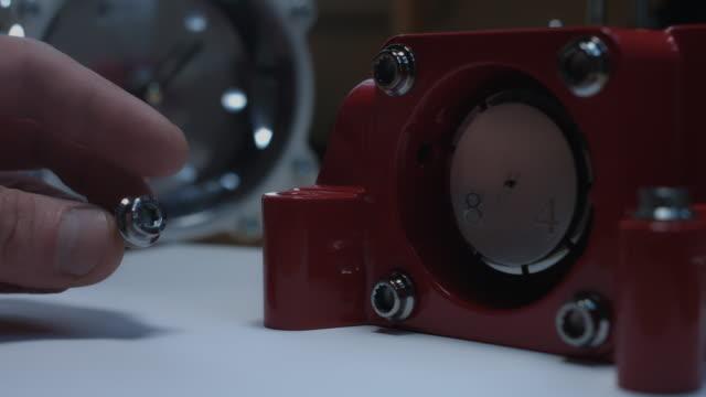 4 k technische zusammensetzung einer menschlichen hand, indem eine schraube in eine handgefertigte uhr - steckschlüssel stock-videos und b-roll-filmmaterial