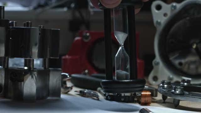 4 k technische zusammensetzung einer menschlichen hand, die platzierung der sand uhr - steckschlüssel stock-videos und b-roll-filmmaterial