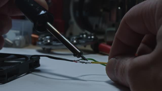 4 k technische zusammensetzung einer menschlichen hand löten drähte - steckschlüssel stock-videos und b-roll-filmmaterial