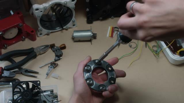 4 k technische zusammensetzung einer menschlichen hand ausziehen die schrauben von ein autoteil - steckschlüssel stock-videos und b-roll-filmmaterial