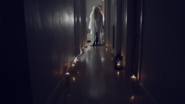 4k Thriller Shot in a Long Hall with Candles, Girl Entering into Darkness Caucasian actress performing. ghost stock videos & royalty-free footage