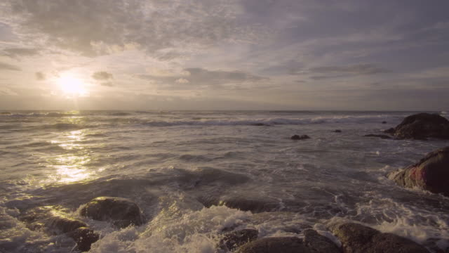 4k tilt down of Sea beach and stone with sunset. video