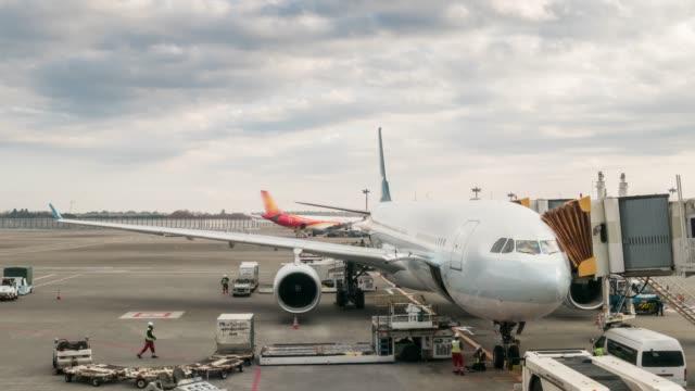 4 k zeitraffer: flugzeug parken an der bucht und bereiten sich auf gepäck zu laden - asphalt stock-videos und b-roll-filmmaterial