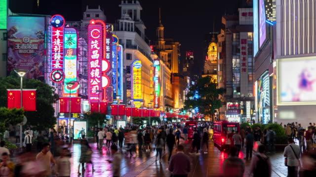 vidéos et rushes de 4k time lapse: public ambulant marchant à nanjing rue commerçante de route qui a décoré avec le drapeau chinois, ville de changhaï, chine. - chine