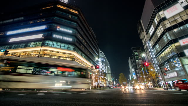 vídeos de stock e filmes b-roll de 4k time lapse : traffic speeds through an intersection in kyoto city. zoom in shot - cidade de quioto