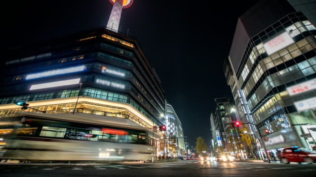 vídeos de stock e filmes b-roll de 4k time lapse : traffic speeds through an intersection in kyoto city. tilt up shot - cidade de quioto