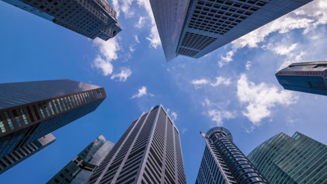 4k time lapse upper view of business and financial skyscraper buildings in singapore. - guardare in su video stock e b–roll