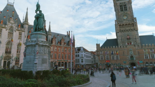 4k timelapse crowd tourists walking in  Grote Markt square and Belfort tower in Bruges, Belgium.