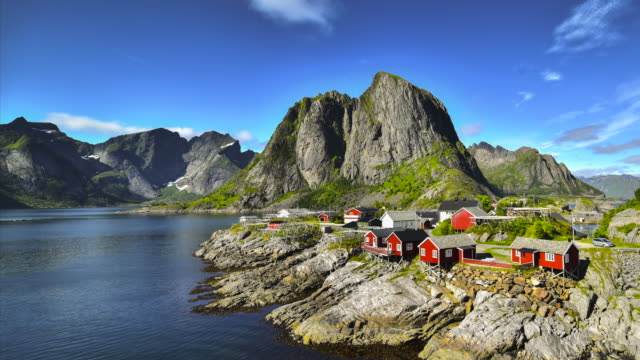 vídeos de stock e filmes b-roll de 4k time-lapse moving clouds over traditional norwegian fisherman's cabins, rorbuer, on the island of hamnoy, reine, lofoten islands, summer of norway. - reine