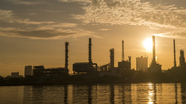 4k timelapse of 4k Oil refinery  petrochemical plant timelapse at sunrise with reflection of river