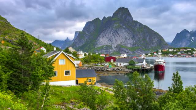 vídeos de stock e filmes b-roll de 4k timelaspe moving clouds over traditional norwegian fisherman's cabins, rorbuer, on the island of hamnoy, reine, lofoten islands, summer of norway. - lofoten
