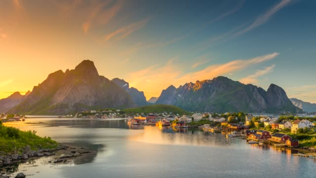 vídeos de stock e filmes b-roll de 4k timelaspe panning of  moving clouds over traditional norwegian fisherman's cabins, rorbuer, on the island of hamnoy, reine, lofoten islands, summer of norway. - fiorde