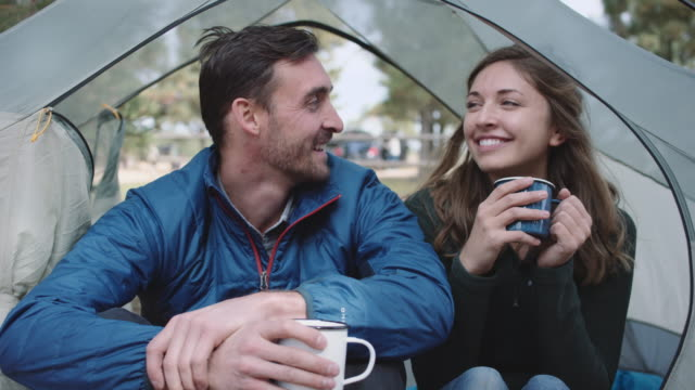 4k UHD: Caucasian couple having hot drinks in their tent