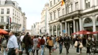 istock 4k uhd slowmotion crowd walking people across street with traffic and facade shop in BRussel belgium famouse destination of europe 1211371394