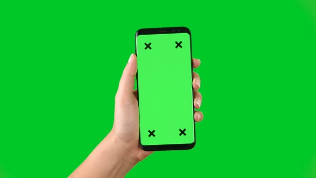 vídeos de stock e filmes b-roll de 4k using smart phone displaying chroma key on green screen - segurar