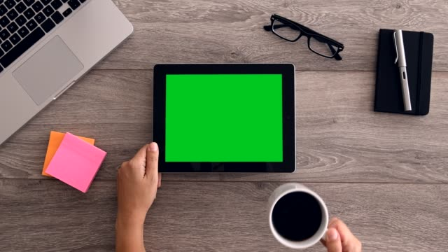 4k using tablet computer displaying green screen Hands  using a tablet pc and scrolling down chroma key screen on a wooden desktop. table top view stock videos & royalty-free footage