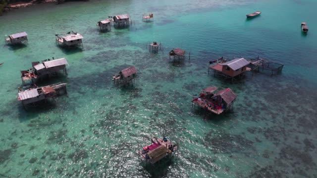 stockvideo's en b-roll-footage met 4k videobeelden van drone van palen huizen en boten in sulawesi zee - maleisië