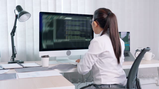 4k video footage of Young Asian Woman Programmer reading and working on computer with coding Development Website design and developing technology