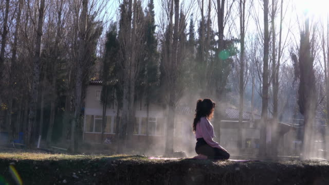 4k Video Of Adult Woman Doing Yoga Exercises In foggy outdoor video
