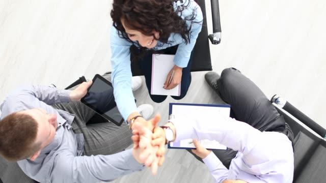 vidéos et rushes de 4k vidéo de travailleurs excités dans le bureau donnant commune high five pour gagner - perfection
