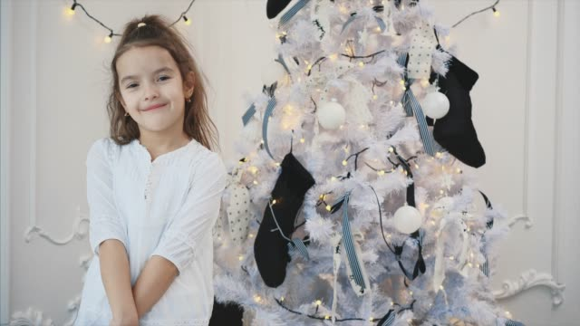 4k video of smiling girl, little snow princess, near christmas tree, giving thumbs up, on a white background.
