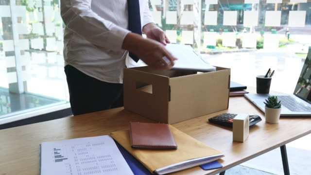 vídeos de stock e filmes b-roll de 4k video of unhappy employee packing his belongings into cardboard box and leaves office - ser despedido