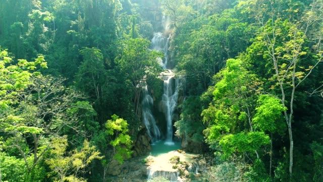 vidéos et rushes de 4 k vidéo shot vue aérienne par drone. chute d'eau de kuang si emblématique nature voyage place de la ville de luang prabang, laos. - pureté