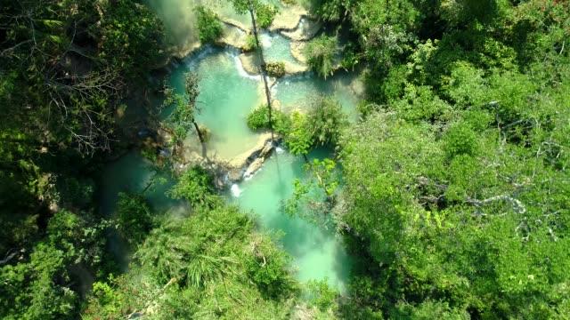 vidéos et rushes de 4 k vidéo shot vue aérienne par drone. chute d'eau de kuang si emblématique nature voyage place de la ville de luang prabang, laos. - forêt tropicale humide