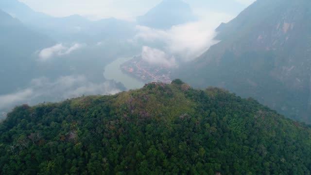 vídeos y material grabado en eventos de stock de 4 k video tiro vista aérea por drone. pico de phadeng en el pueblo de nong khiaw, río, colinas, luang pranbang, laos. - sudeste
