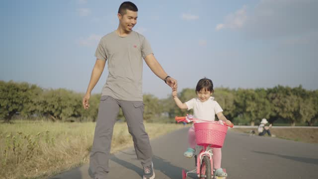 4k Video slow-motion, An Asian father teaching his daughter how to ride a bicycle on a park road During holiday time. Family concept.