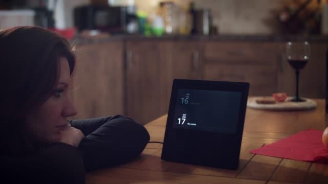 vídeos de stock e filmes b-roll de 4k woman checking calendar on smart home device - controlo