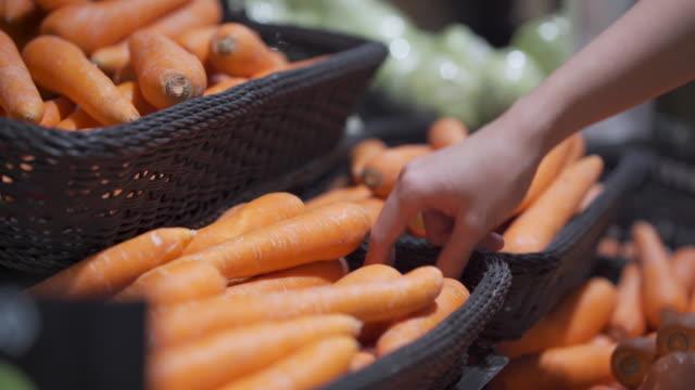 4k kvinna hand välja morötter ur korg hyllan på super marknaden livsmedelsbutik hylla, färska grönsaker, livsstil hälsosam kost, ekologiska produkter, veggie mat recept meny, ingrediens vitamin - morot bildbanksvideor och videomaterial från bakom kulisserna