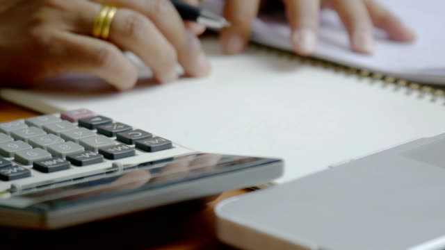 4k Woman using calculatior of financial data analyzing. Hand with pen on calculator. video