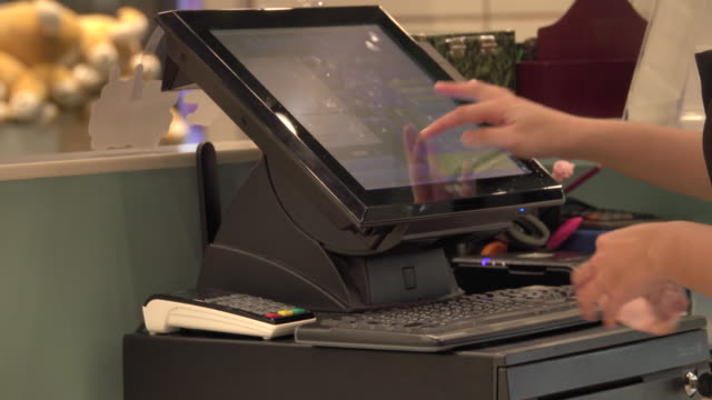4k: worker using touchscreen cash register at cashier