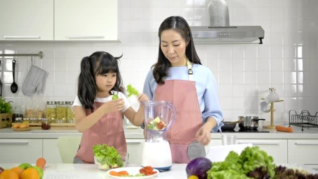 4k, giovane madre e figlia asiatica felice e divertente preparando insalata di frutta e verdura in una moderna cucina bianca.figlia allegra quando si cucina. - cucina vegetariana video stock e b–roll