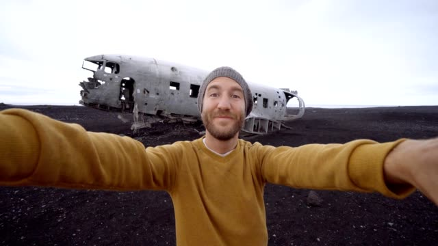 4k- Young man standing by airplane wreck on black sand beach taking a selfie portrait Famous place to visit in Iceland and pose with the wreck video