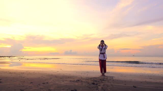 vídeos de stock, filmes e b-roll de 4k: mulheres jovens practising artes marciais ao ar livre na praia ao pôr do sol - artes marciais