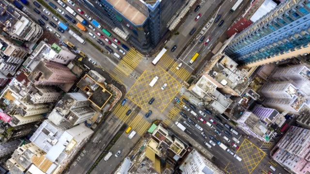 4k zoom out hyperlapse of urban crossing road direct above in day, hong kong - пик стоковые видео и кадры b-roll