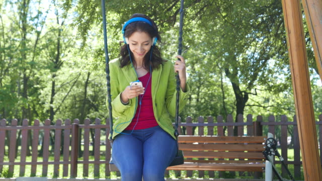 4K_Girl listening to music on a swing