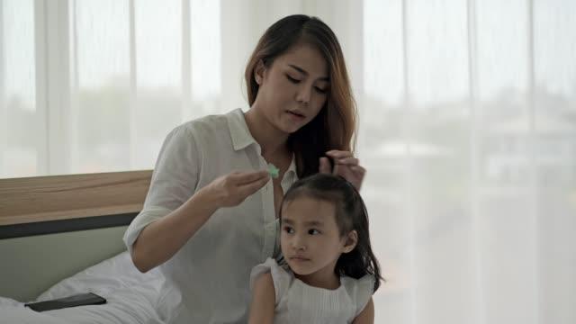 4k, asiatisk familj, mor borsta hennes dotters hår när du sitter på sängen hemma. - cosy pillows mother child bildbanksvideor och videomaterial från bakom kulisserna