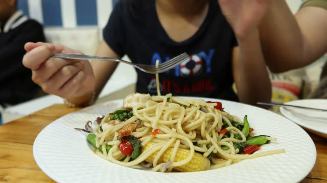 4K,Asian girl twist spaghetti in white dish and eating